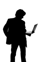 Silhouette of a man in suit holding laptop