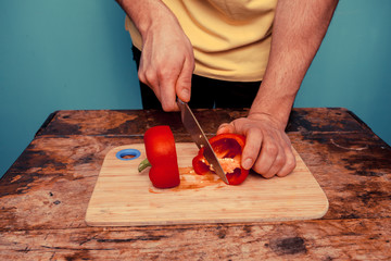 Young man cutting a bell pepper