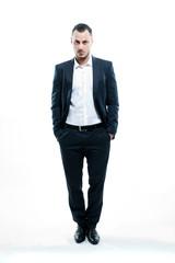 Junger Mann im Anzug, stehend vor weißem Hintergrund