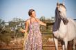 junge weibliche reiterin trainiert ihr pferd im freien im sommer - 61026231