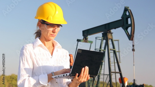 Business woman in an oilfield working with notebook