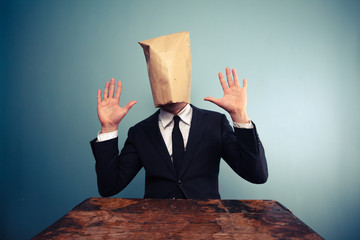 Startled businessman with bag over head raising his hands