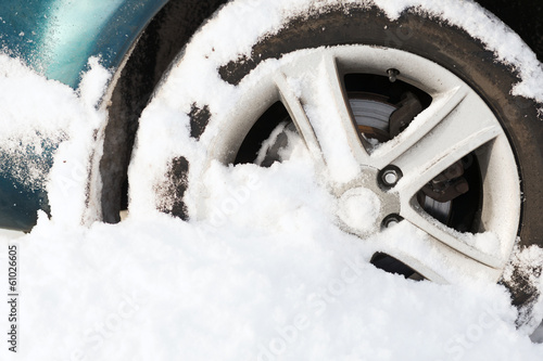 closeup of car wheel stuck in snow