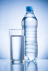 Plastic bottle and glass of drinking water isolated on blue back