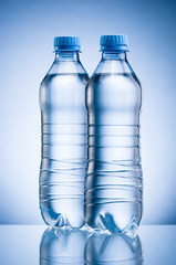 Two plastic bottle of drinking water isolated on blue background