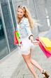 junge lachende blonde frau mit bunten einkaufstaschen