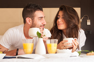 Young couple having breakfast in luxury hotel room.
