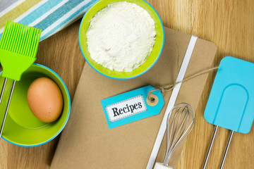 egg, flour and kitchen utensils on recipe book