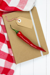 notebook with chili peper and tea towel