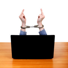 Handcuffs on Hands behind Laptop
