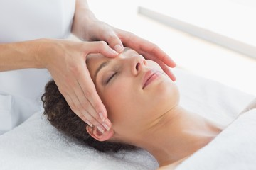 Woman receiving massage on forehead