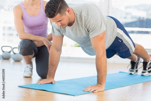 Trainer assisting man with push ups