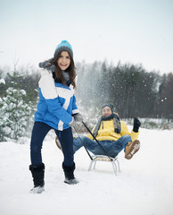 Couple have fun on sled in winter time