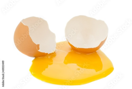 A broken egg with yolk on a white background