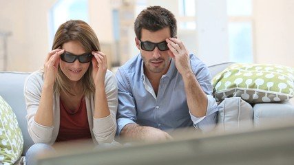 Couple at home watching 3D movie with eyeglasses