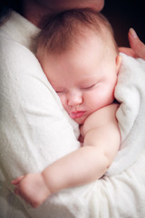 baby sleep on hands of mother
