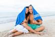 lachendes junges verliebtes paar mit einem handtuch am strand