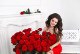 Beautiful smiling brunette woman with red roses bouquet, valenti