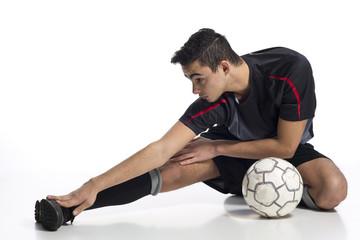 junger Nachwuchsspieler Fussballer beim Dehnen