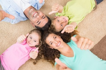 Smiling family lying on the rug in a circle showing thumbs up