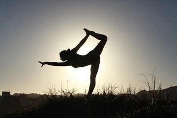 Silhouette of acrobatic teen gymnast balancing with the sun behi