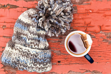 Cosy winter hat with a cup of fresh hot tea