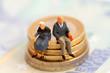 Leinwanddruck Bild Senioren sitzen auf Muenzstapel