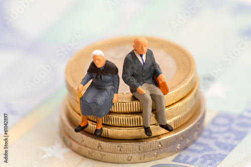Leinwanddruck Bild - blende40 : Senioren sitzen auf Muenzstapel