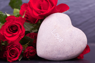 stone heart with red roses on black schist