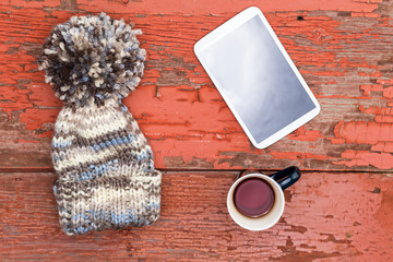 Cozy winter cap, tablet and tea on a grungy table