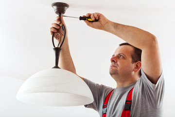 Electrician mounting ceiling lamp