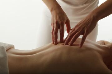 Massage therapist performing back massage.