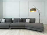 Gray couch and floor lamp against white wall