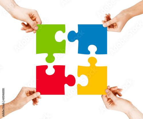four hands connecting puzzle pieces
