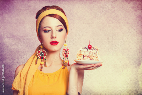 Style redhead girl with cake at pink background.