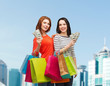 smiling teenage girls with shopping bags and money