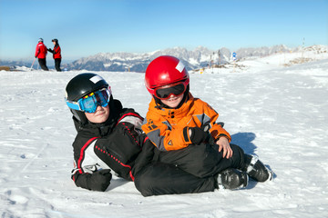 Two boys play on mountain summit in Alps, Kitzbuhel, Austria