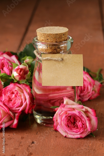 essence of rose flowers in a glass bottle