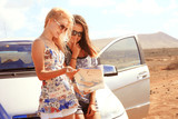 Two young women with car look at road map with mountain landscap