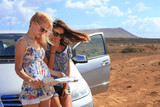 Two young women with car look at road map on a beach against sea
