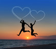 Loving couple flying it sky against sea beachand heart-shaped va