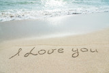 "words ""I love you"" outline on wet sand with wave brilliance"