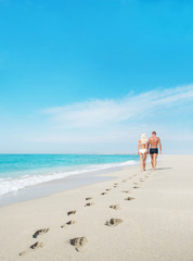 loving couple walking with footprints at sea sandy beach