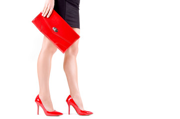Beautiful slender  women's  legs in red shoes and mini bag