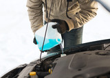 closeup of man pouring antifreeze into water tank