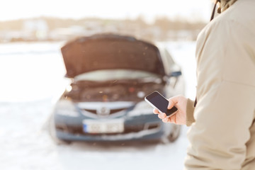 closeup of man with broken car and smartphone