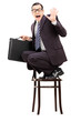 Terrified businessman holding briefcase standing on a chair