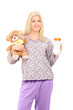 Young woman in pajamas holding teddy bear and baby bottle