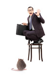 Terrified young businessman holding briefcase standing on chair