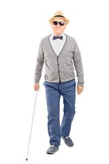 Blind senior gentleman walking with a stick